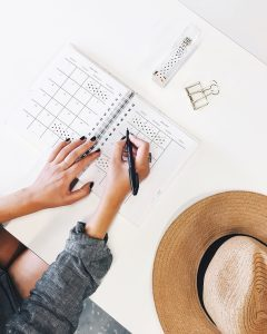 woman filling out a planner - cope with moving stress