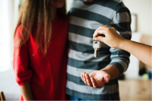 woman giving keys to a couple